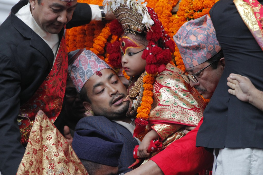 A devotee carries a revered living goddess Kumari, center, to a chariot during Indra Jatra festival, an eight-day festival that honors Indra, the Hind...