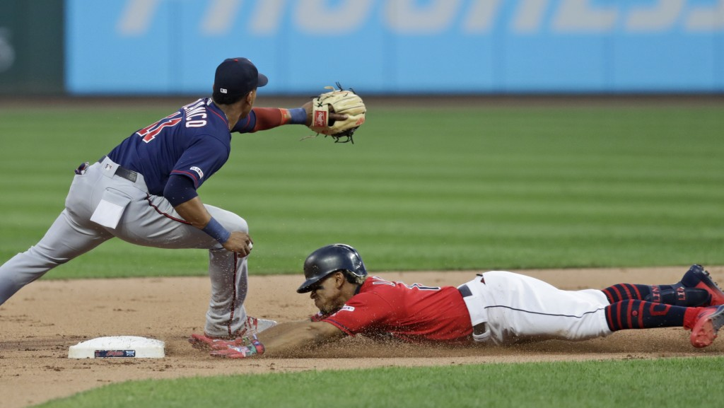 Cleveland Indians' Francisco Lindor, right, slides safely into second base for a double as Minnesota Twins' Jorge Polanco waits for the ball in the fi...