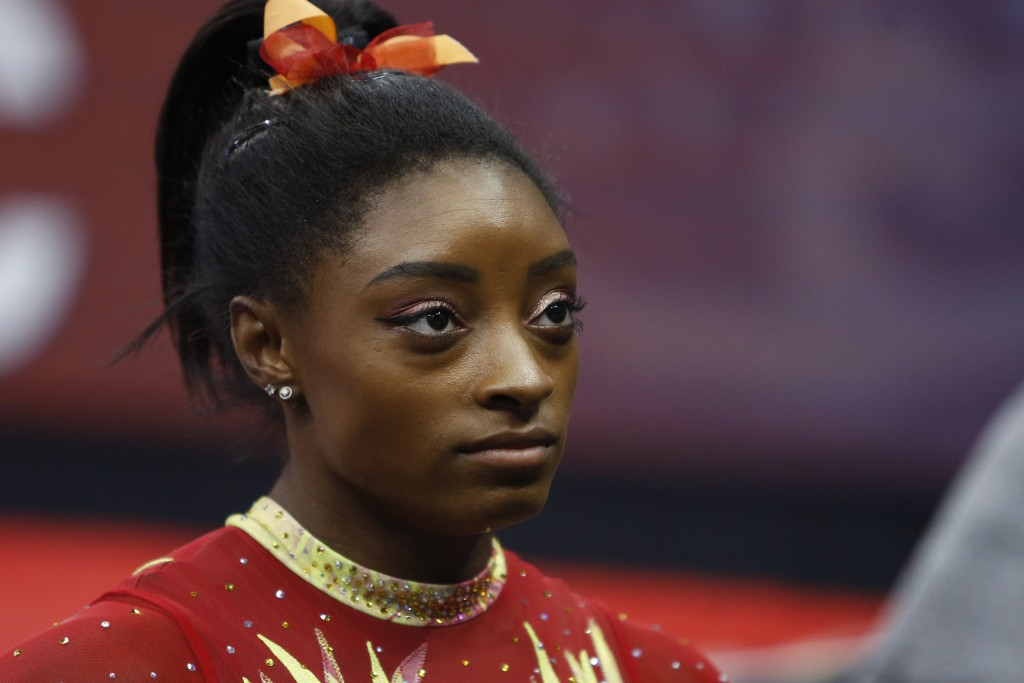 FILE - In this July 28, 2018, file photo, Olympic champion Simone Biles talks with her coach before the start of the U.S. Classic gymnastics competiti...