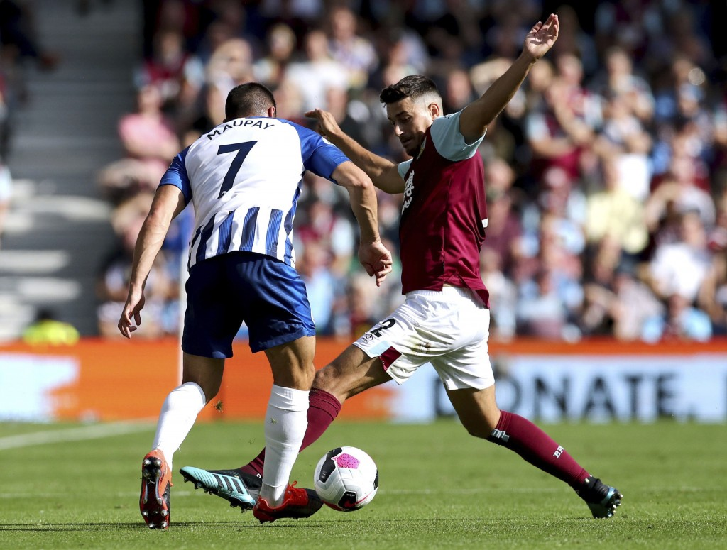 Brighton and Hove Albion's Neal Maupay, left, and Burnley's Matthew Lowton battle for the during the English Premier League soccer match between Brigh...