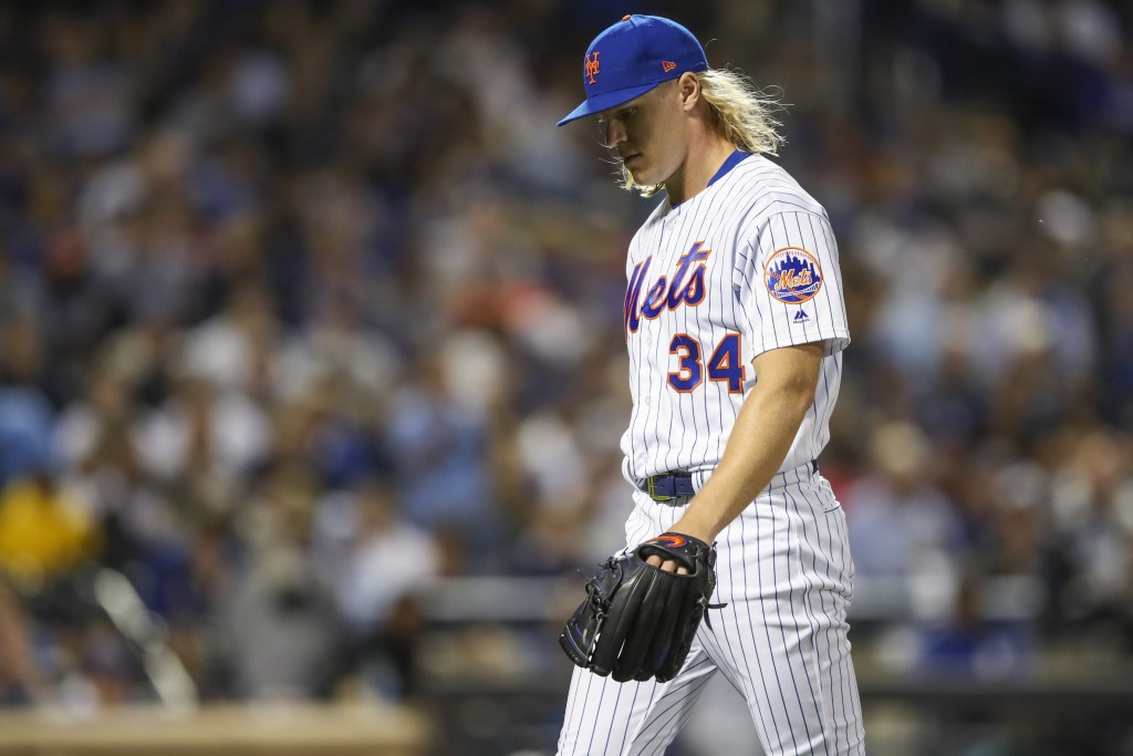 New York Mets starting pitcher Noah Syndergaard walks off the field after the top of the fourth inning of the team's baseball game against the Los Ang...