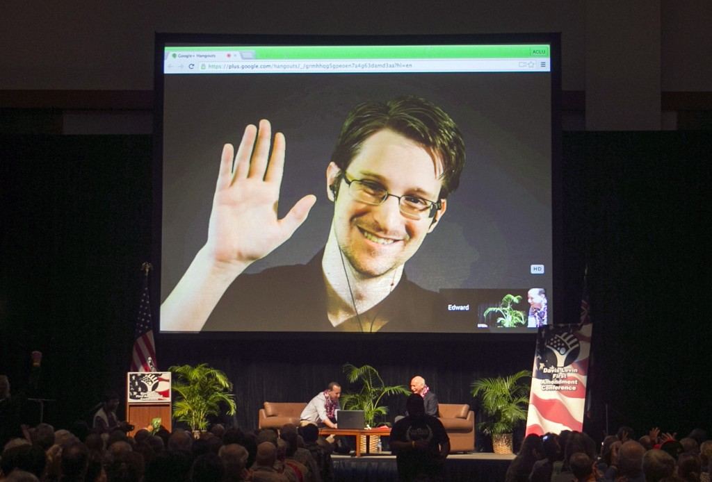 FILE - In this Feb. 14, 2015, file photo, Edward Snowden appears on a live video feed broadcast from Moscow at an event sponsored by ACLU Hawaii in Ho...