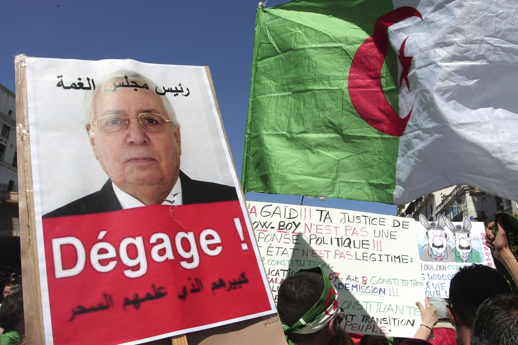 """FILE - In this April 26, 2019 file photo, a demonstrator holds a placard showing Abdelkader Bensalah and reading """"Get out"""" during a protest in Algiers"""