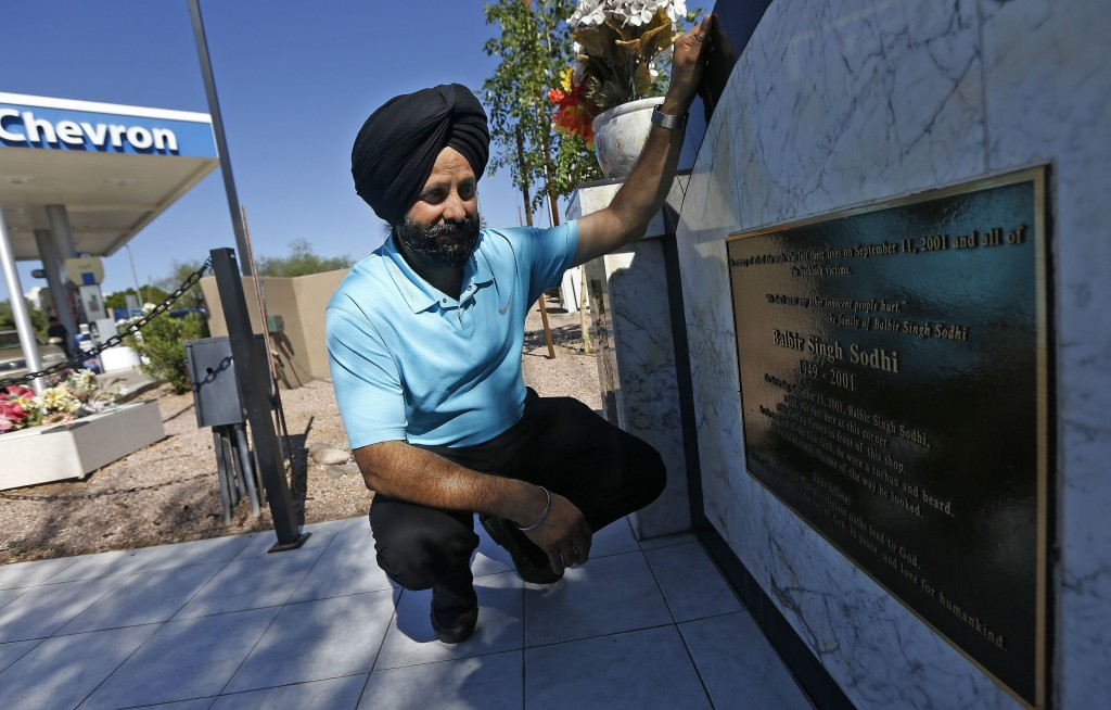 FILE - In this Aug. 19, 2016, file photo, Indian Sikh immigrant Rana Singh Sodhi kneels next to a memorial in Mesa, Ariz., for his murdered brother, B