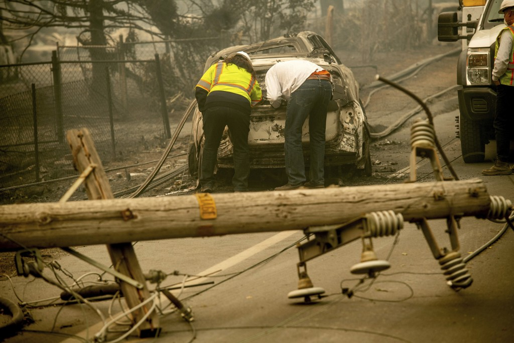 FILE - In this Nov. 10, 2018 file photo, with a downed power utility pole in the foreground, Eric England, right, searches through a friend's vehicle