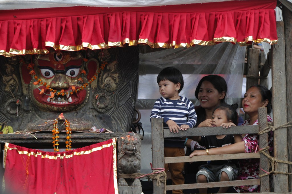 Devotees sit next to a statue of god Bhairabh during Indra Jatra festival, an eight-day festival that honors Indra, the Hindu god of rain, in Kathmand