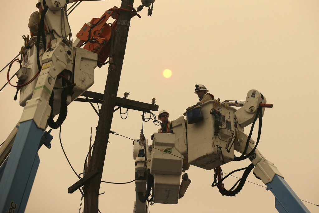 FILE - In this Nov. 9, 2018 file photo, Pacific Gas & Electric crews work to restore power lines in Paradise, Calif.  Pacific Gas & Electric has agree...
