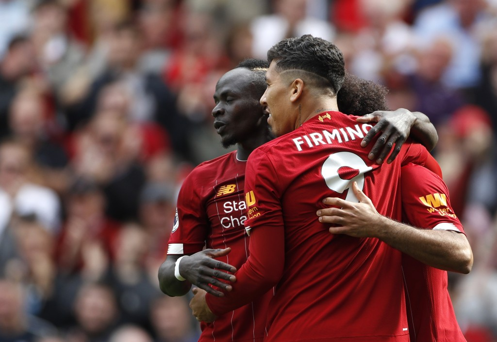 Liverpool's Sadio Mane, left, celebrates with Liverpool's Roberto Firmino, center, and Liverpool's Mohamed Salah, right, after scoring his sides secon