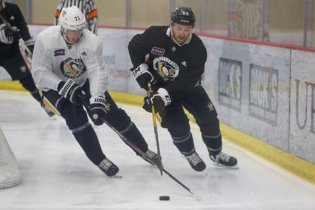 Pittsburgh Penguins' Evgeni Malkin, left, takes the puck from David Warsovsky during NHL hockey practice on the team's first day of training camp, Fri