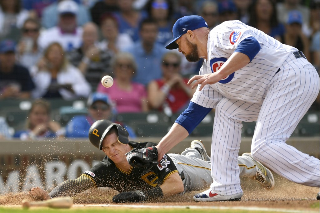Pittsburgh Pirates' Kevin Newman left, slides safely into home plate on a throwing error by Chicago Cubs center fielder Albert Almora Jr. as Chicago C