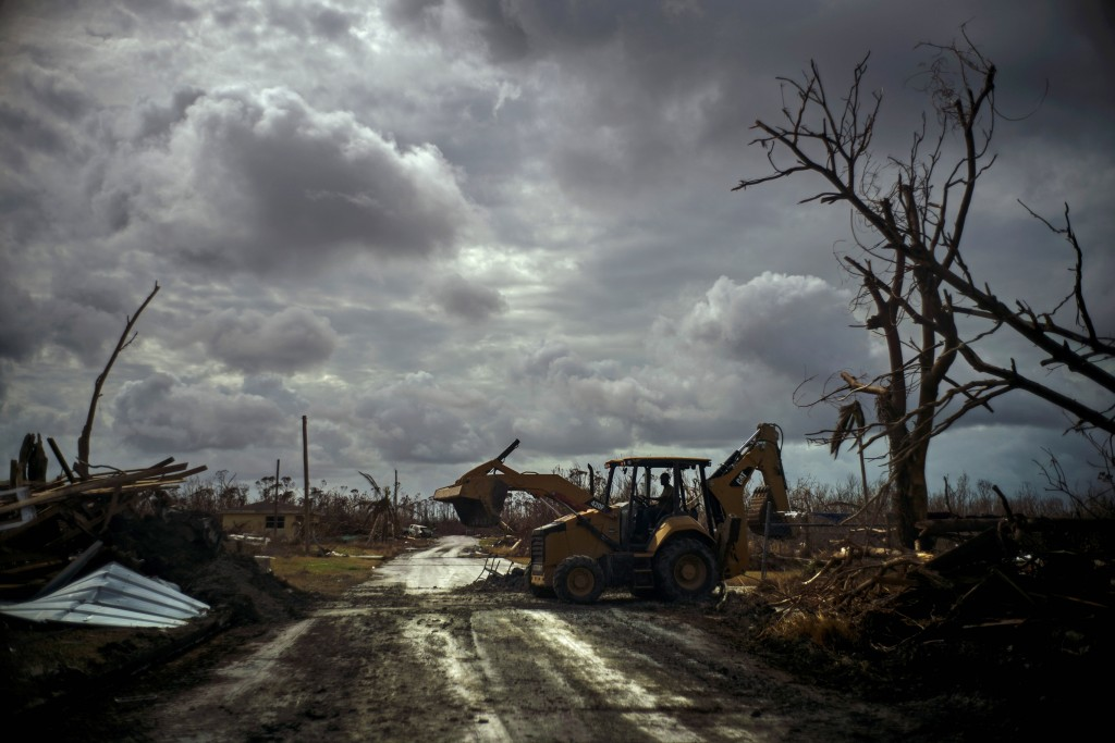 Mos Antenor, 42, drives a bulldozer while clearing the road after Hurricane Dorian Mclean's Town, Grand Bahama, Bahamas, Friday Sept. 13, 2019. (AP Ph...