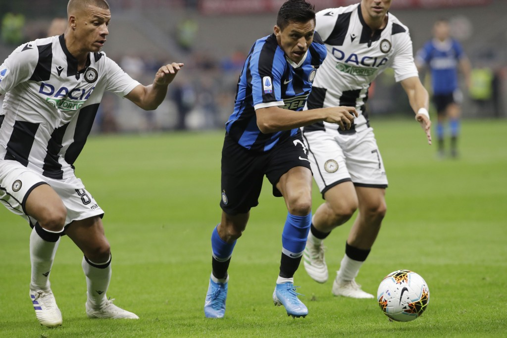 Inter Milan's Alexis Sanchez challenges for the ball with Udinese's Antonin Barak during a Serie A soccer match between Inter Milan and Udinese, at th