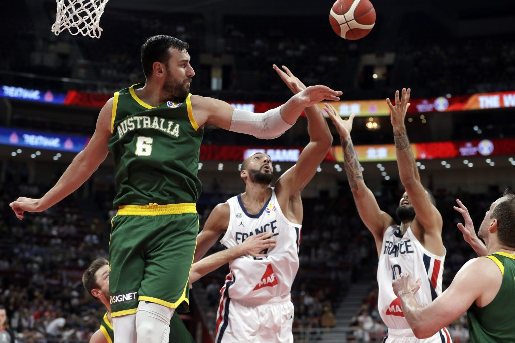 Andrew Bogut of Australia and Rudy Gobert, center, and Evan Fournier of France battle for the ball during their third-place match in the FIBA Basketba