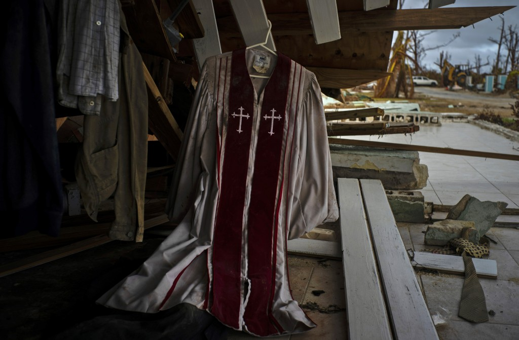 Priest's mass vestments hang in the rubble of a destroyed house by Hurricane Dorian in Pelican Point, Grand Bahama, Bahamas, Saturday Sept. 14, 2019. ...