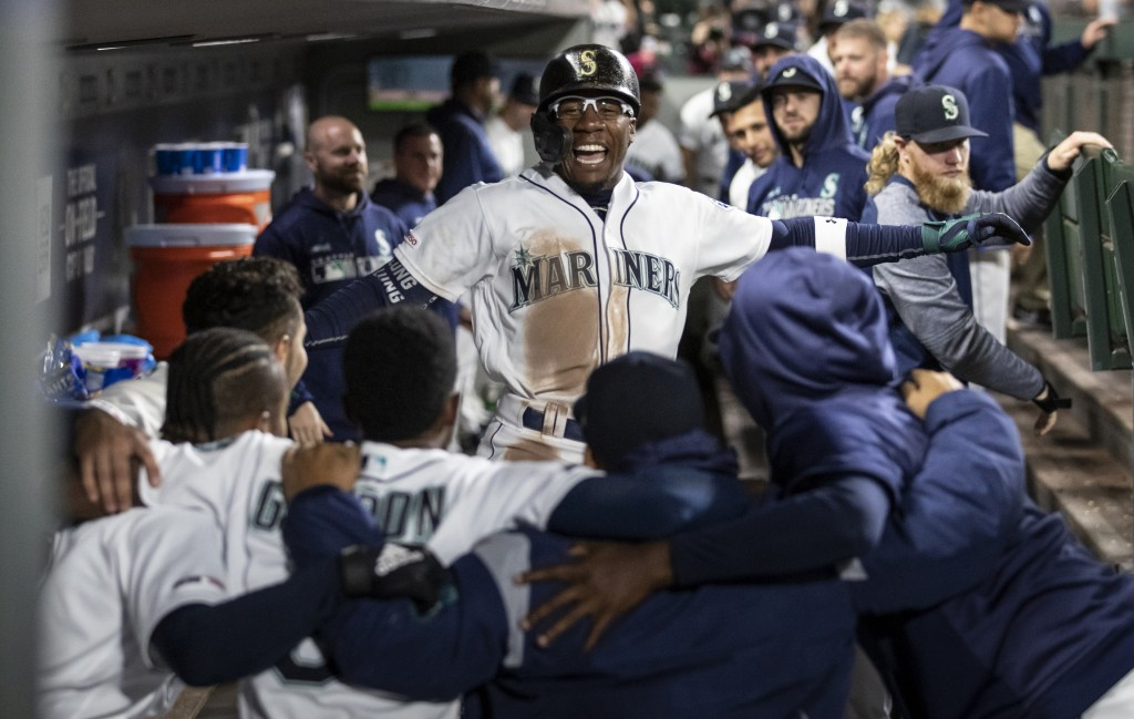 Seattle Mariners' Shed Long is congratulated by teammates in the dugout after hitting a solo home run off Chicago White Sox starting pitcher Dylan Cea...