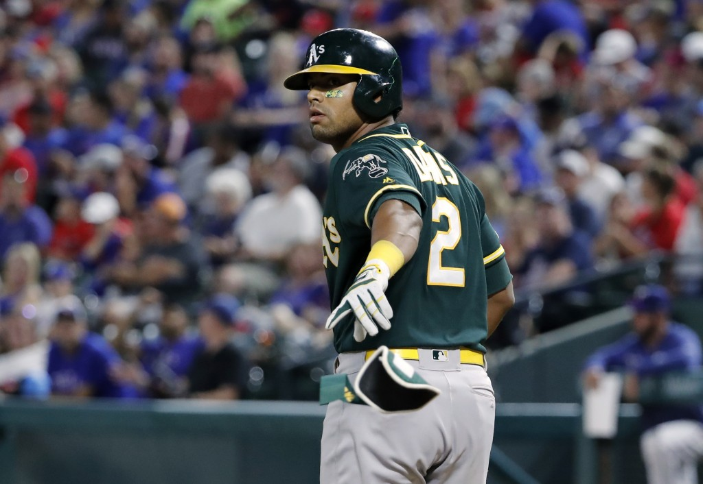 Oakland Athletics' Khris Davis tosses his batting gear after earning a walk in the fifth inning of a baseball game against the Texas Rangers in Arling