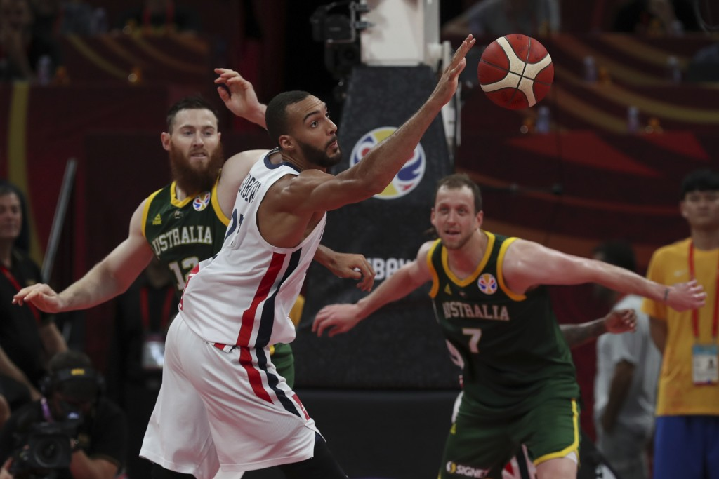 Rudy Gobert of France reaches for the ball over Aron Baynes, left, and Joe Ingles, right, of Australia during their third placing match for the FIBA B