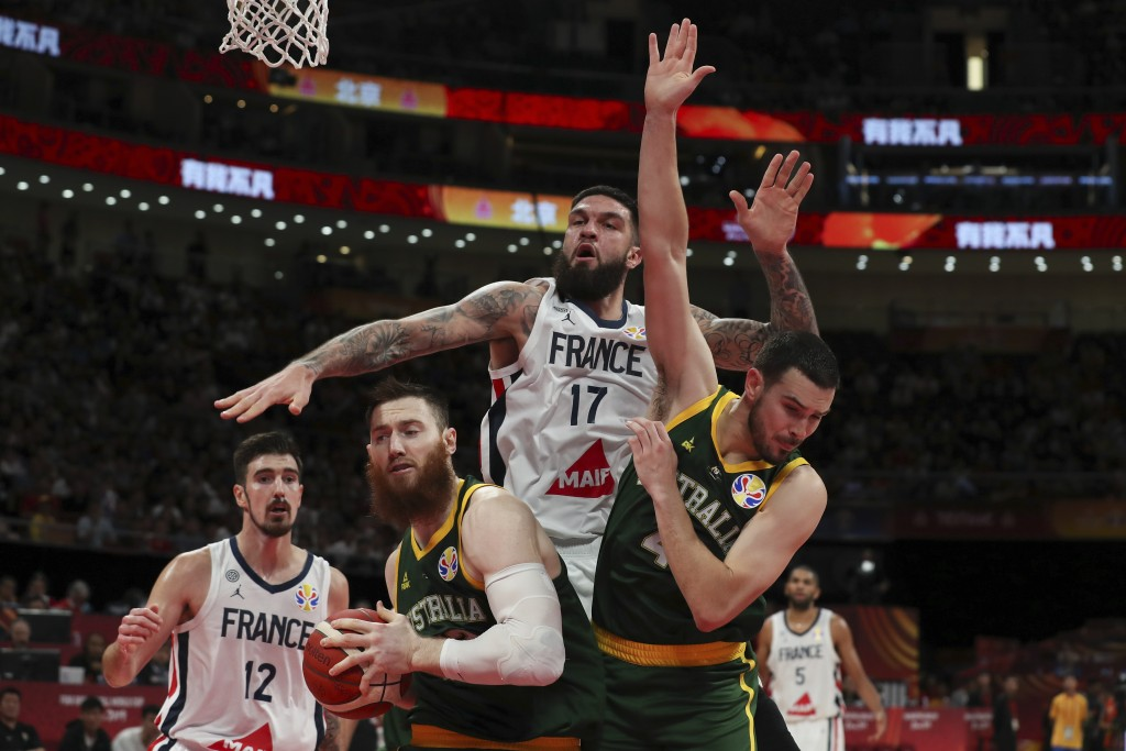 Vincent Poirier of France battles the ball with Aron Baynes and Chris Goulding of Australia during their third placing match for the FIBA Basketball W