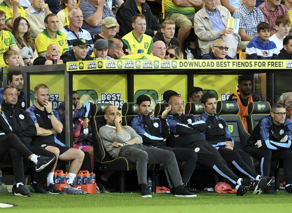 Manchester City manager Pep Guardiola, center left, looks dejected on the bench with his backroom staff during the English Premier League soccer match...