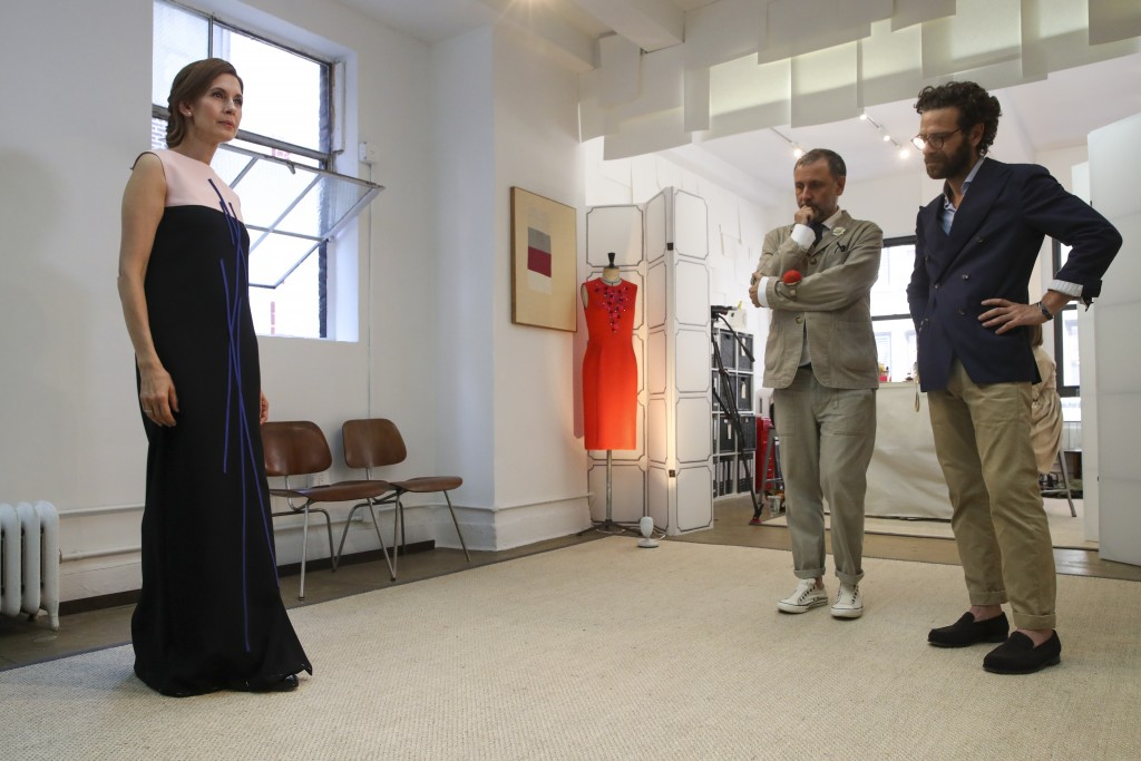 In this Sept. 4, 2019, photo, designer Herve Pierre, center, and Nicolas Caito, right, fit Emmy-nominated actress Jessica Hecht with a dress for her t...