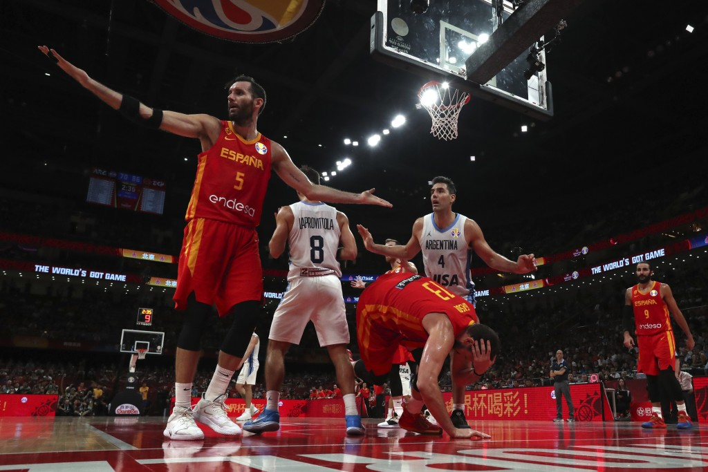 Spain's Marc Gasol center tumbles as teammate Rudy Fernandez, at left, and Argentina's Luis Scola, center in white, react during the final of the FIBA...