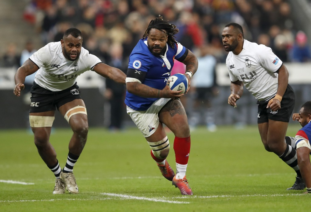 FILE - In this Nov. 24, 2018 file photo, France's Mathieu Bastareaud, centre, runs between Fijian defenders during the rugby international between Fra