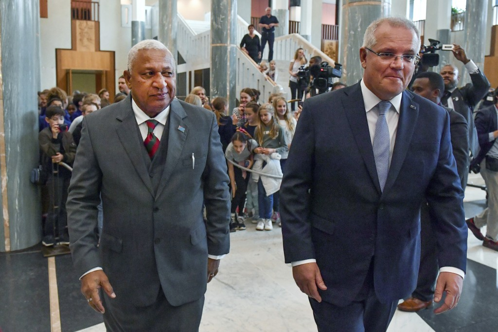 Australia's Prime Minister Scott Morrison, right, and Fiji's Prime Minister Voreqe Bainimarama walk through Parliament House after an official welcome