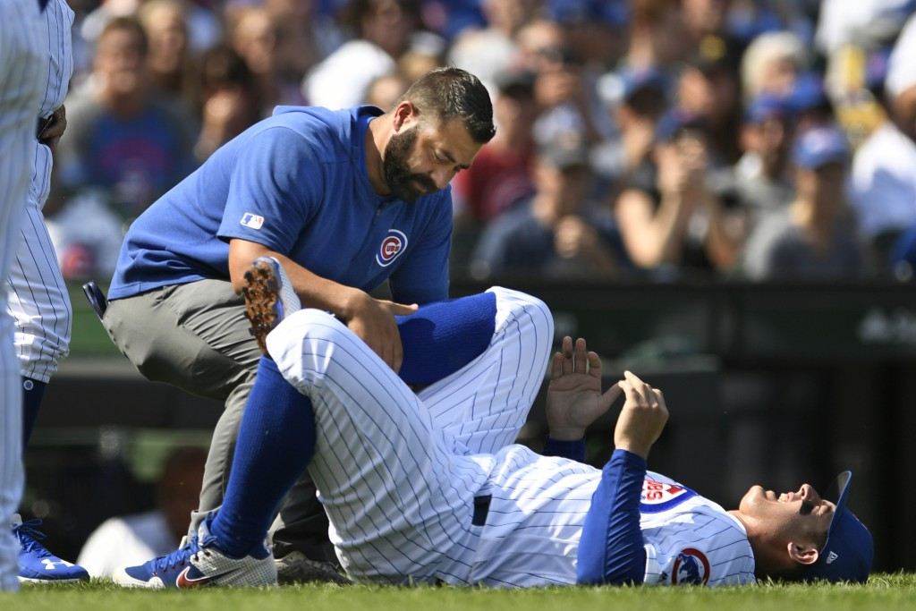 Chicago Cubs' Anthony Rizzo is tended to after spraining his ankle during the third inning of a baseball game against the Pittsburgh Pirates Sunday, S...