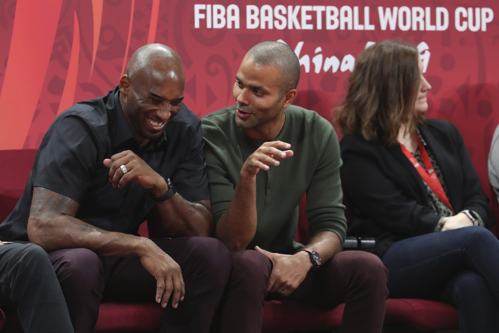Former NBA players Kobe Bryant, left, and Tony Parker talk during the first-place match between Spain and Argentina in the FIBA Basketball World Cup a