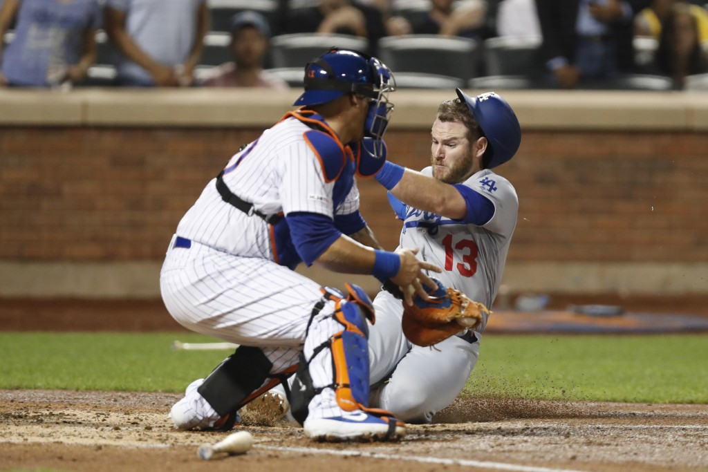 New York Mets catcher Wilson Ramos, left, has the ball in his glove but cannot make the tag in time as Los Angeles Dodgers' Max Muncy (13) scores on C...