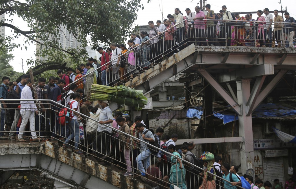 FILE - In this July 5, 2019, file photo, commuters walk on an overbridge at a train station in Mumbai, India. India's labor-intensive manufacturing se...