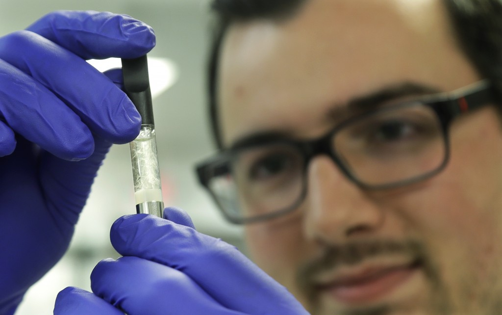 Pierce Prozy examines a Yolo! brand CBD vape oil cartridge at Flora Research Laboratories in Grants Pass, Ore., on July 19, 2019. The Associated Press...