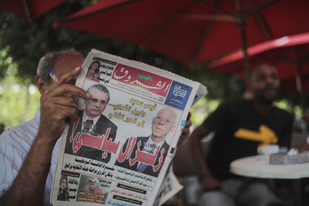 A man reads Al-Shorouk daily newspaper showing candidates Kais Saied, right, ) and Nabil Karoui on its front-page, a day after the first round of pres...