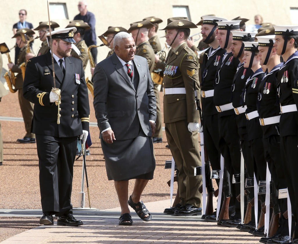 Fiji's Prime Minister Voreqe Bainimarama, center, inspects an honor guard outside Parliament House in Canberra, Australia, during his official welcome