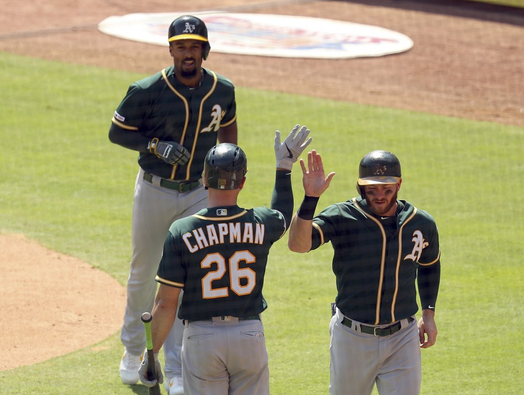 Oakland Athletics Matt Chapman (26) greets Robbie Grossman (8) and Marcus Semien (10) after Semien's two-run home run in the third against the Texas R