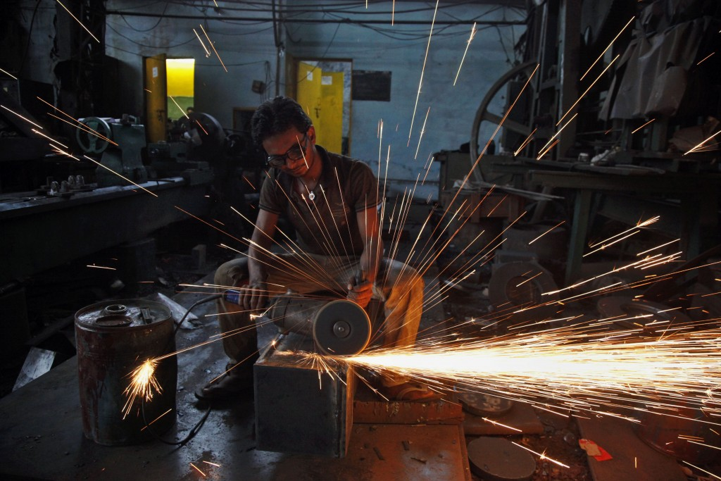 FILE - In this April 15, 2015, file photo, a man uses a metal grinder at a manufacturing factory in Ahmadabad, India. India's labor-intensive manufact...