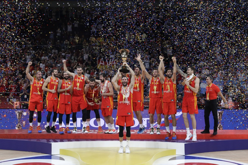 Members of Spain's team celebrate with the Naismith Trophy after they beat Argentina in their first-place match in the FIBA Basketball World Cup at th...