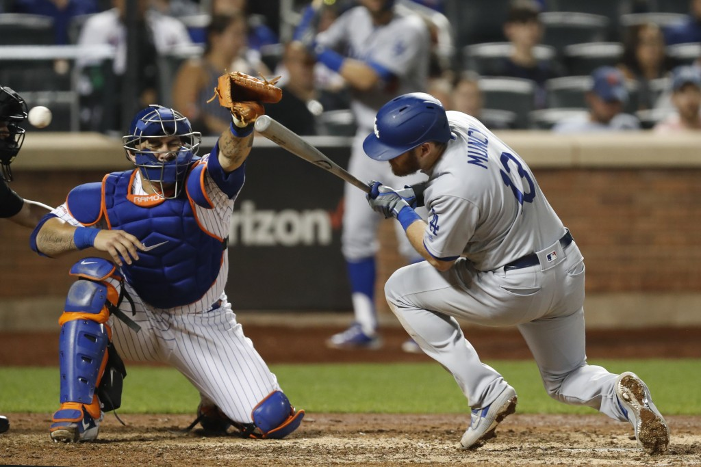 The ball whizzes past New York Mets catcher Wilson Ramos, left, as Los Angeles Dodgers' Max Muncy (13) ducks to avoid a high pitch in the eighth innin...