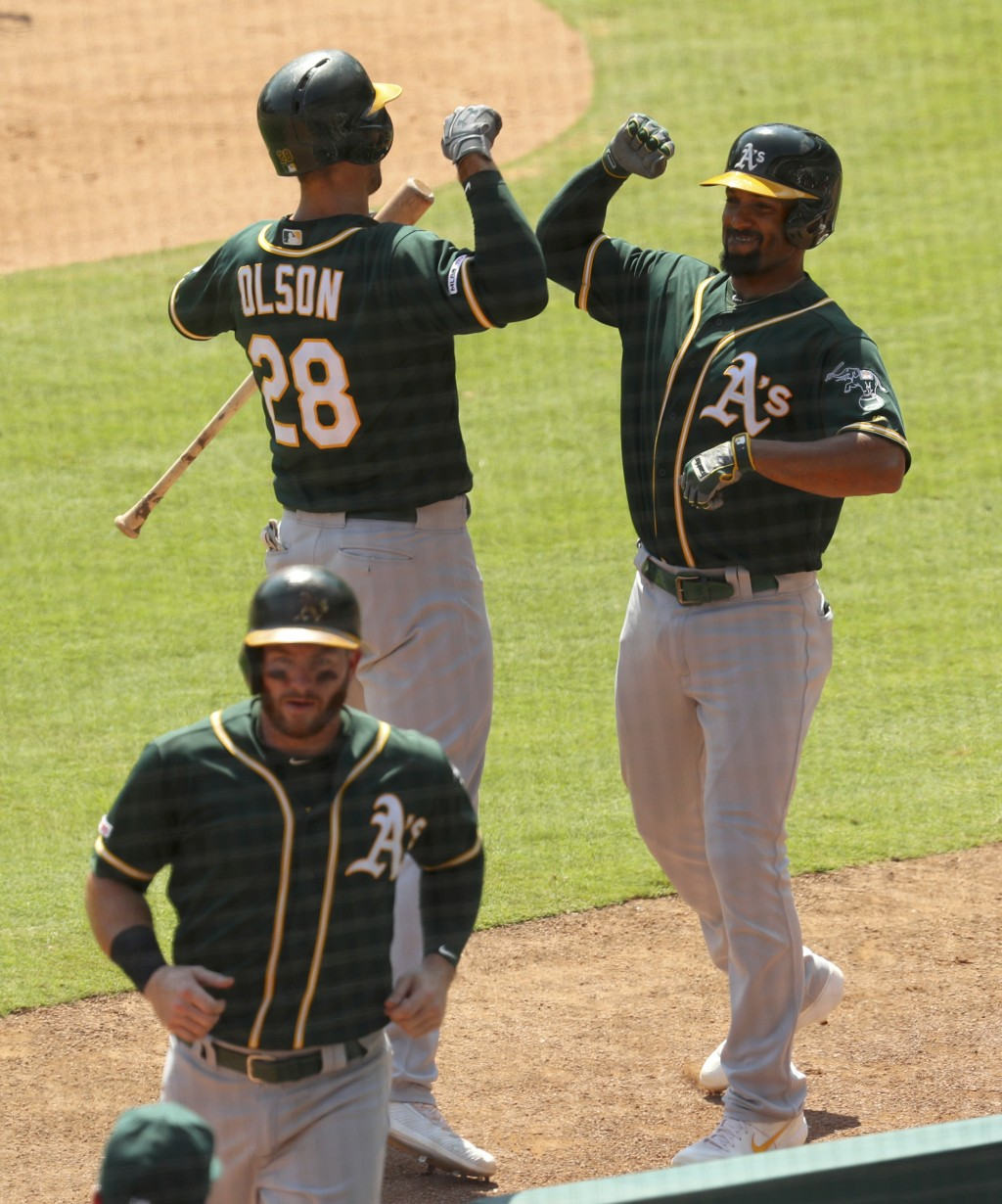Oakland Athletics Matt Olson (28) bumps elbows with Marcus Semien (10) after his two-run home run against the Texas Rangers in the third inning in a b