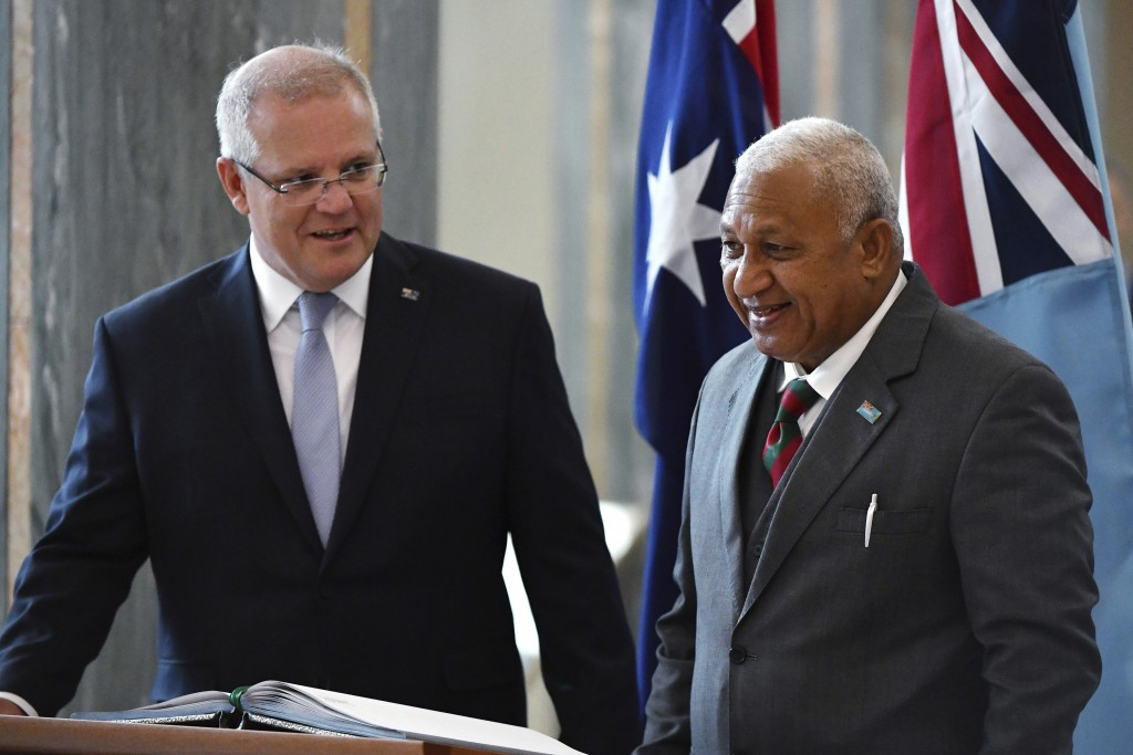 Australia's Prime Minister Scott Morrison, left, watches as Fiji's Prime Minister Voreqe Bainimarama signs the visitors book after an official welcome...