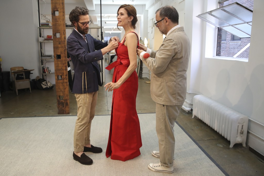 In this Sept. 4, 2019, photo, designer Herve Pierre, right, and Nicolas Caito fit actress Jessica Hecht, for dresses for her to wear at the Creative A...