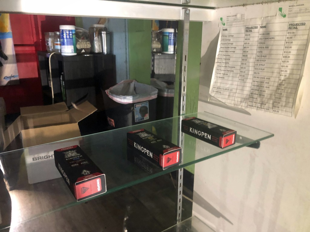 In this Aug. 28, 2019, photograph, boxes of what appear to be Kingpen marijuana vape cartridges are displayed in an illegal dispensary in Los Angeles