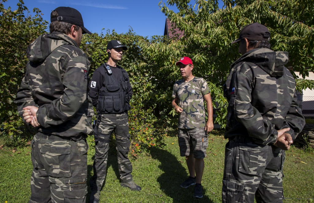 In this Sept. 4, 2019 photo, Andrej Sisko, center right, leader of volunteer group called the Stajerska Garda talks to his lieutenants in Maribor, Slo...