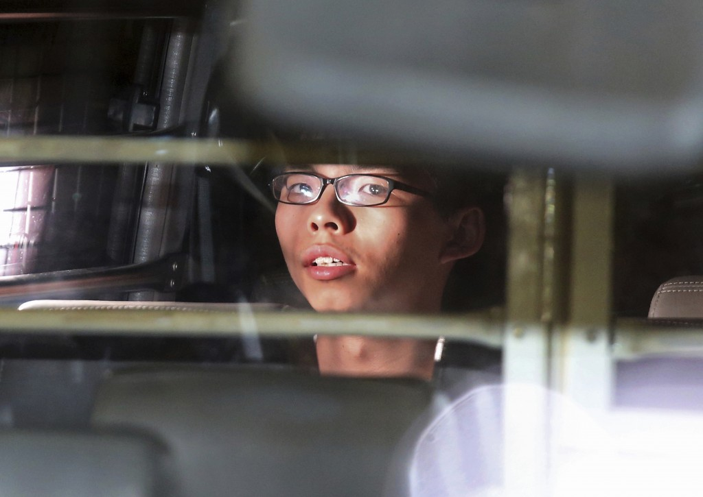 FILE - In this Aug. 17, 2017, file photo, Hong Kong activist Joshua Wong is taken away in a prison bus leaving the high court after his sentencing in