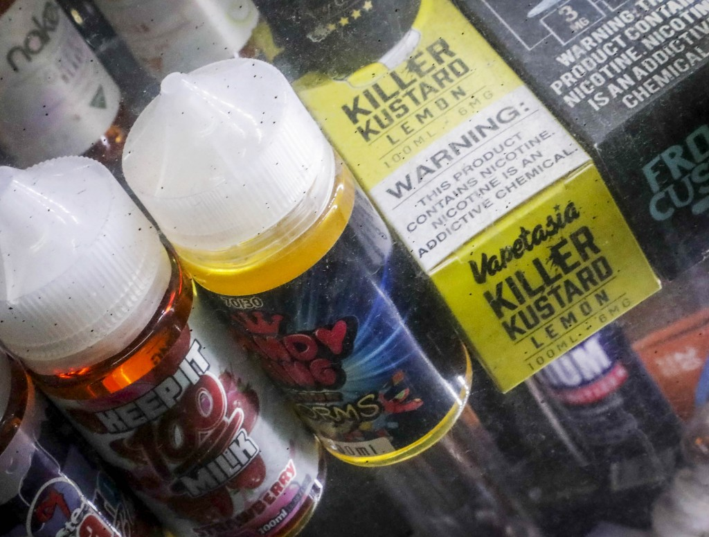Flavored vaping solutions are shown in a window display at a vape and smoke shop, Monday Sept. 16, 2019, in New York. New York Gov. Andrew Cuomo is pu...