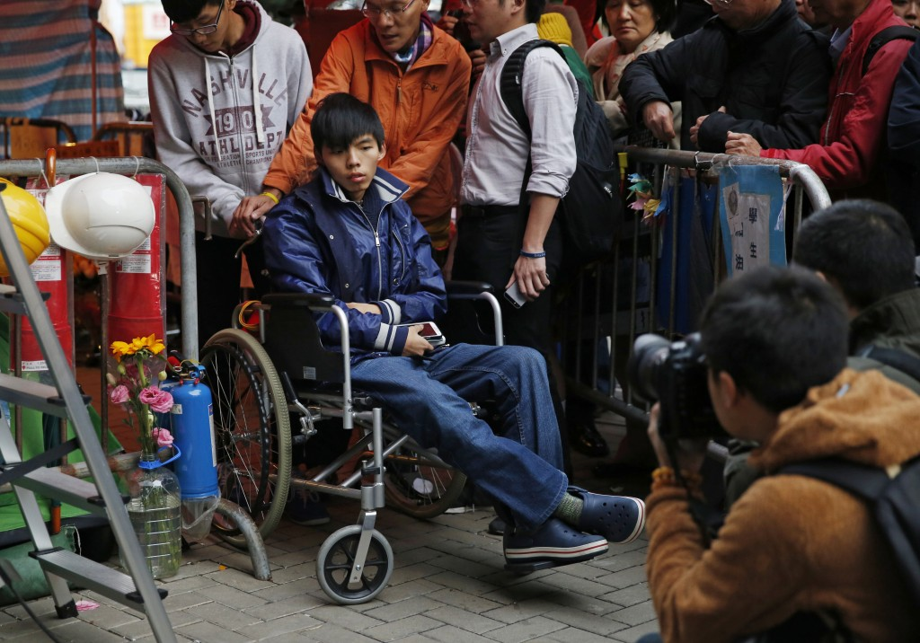 FILE - In this Dec. 5, 2014, file, photo, student leader Joshua Wong attends a news conference as he sits on a wheel chair during a hunger strike at t