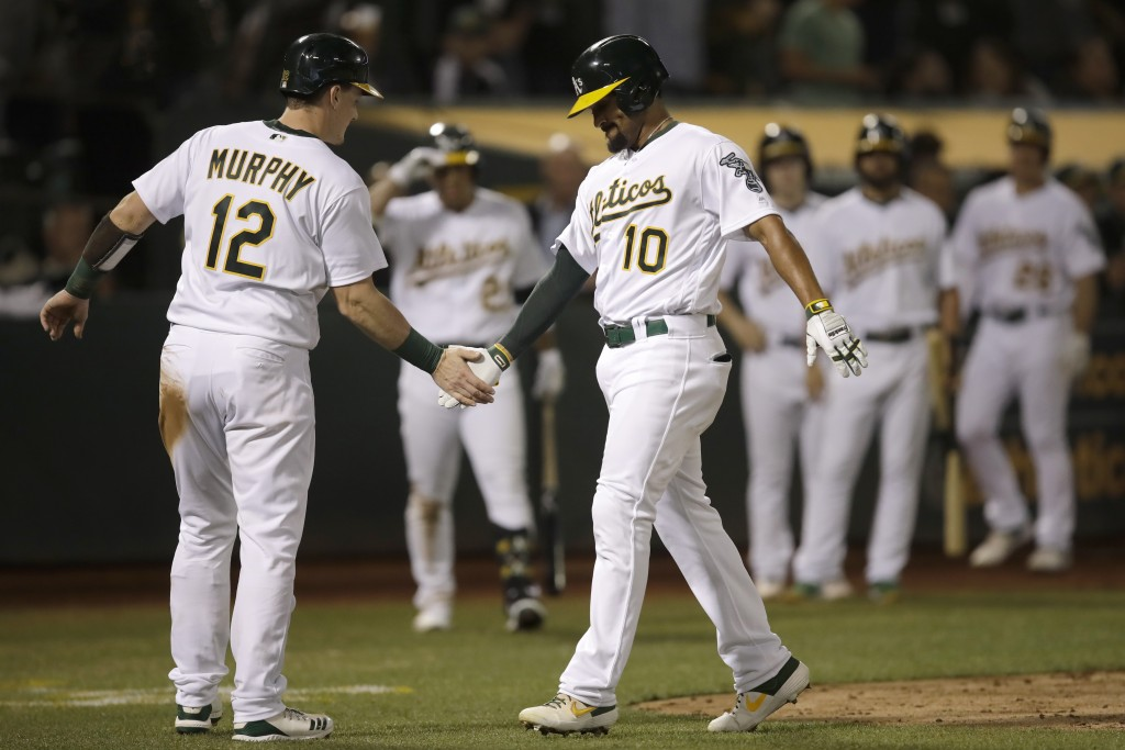 Oakland Athletics' Marcus Semien, right, is congratulated by Sean Murphy (12) after hitting a two-run home run against the Kansas City Royals in the s
