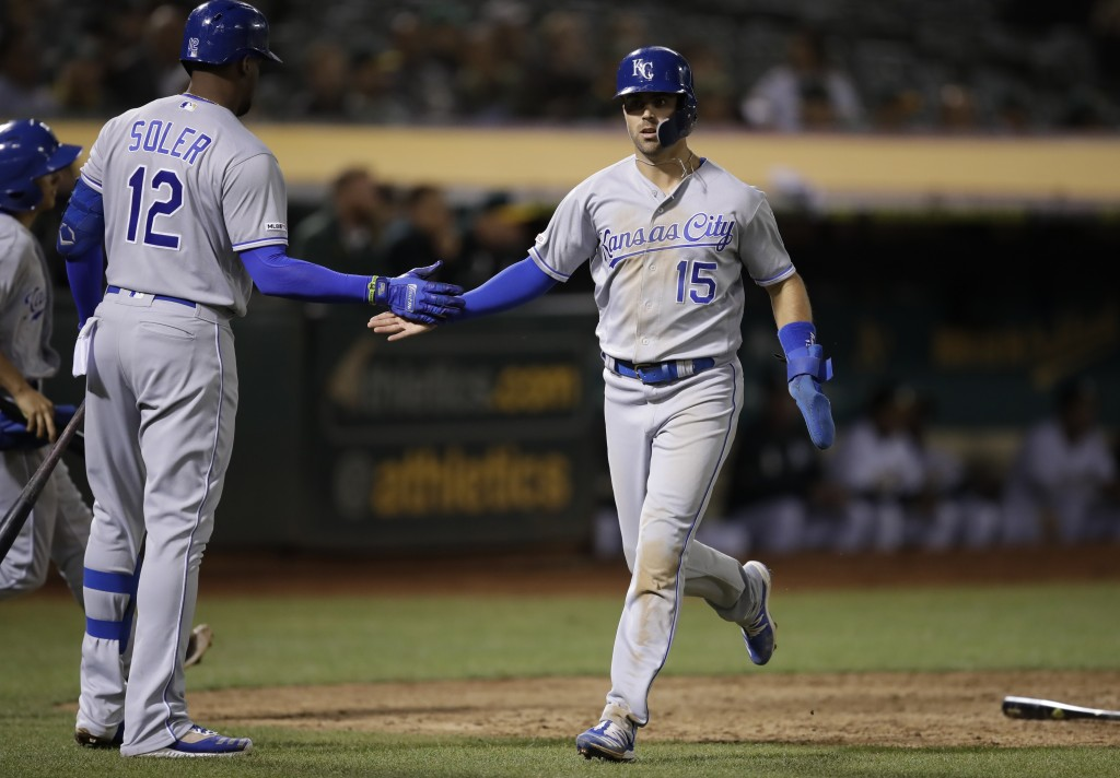 Kansas City Royals' Whit Merrifield, right, celebrates with Jorge Soler (12) after scoring the game-winning run against the Oakland Athletics in the n