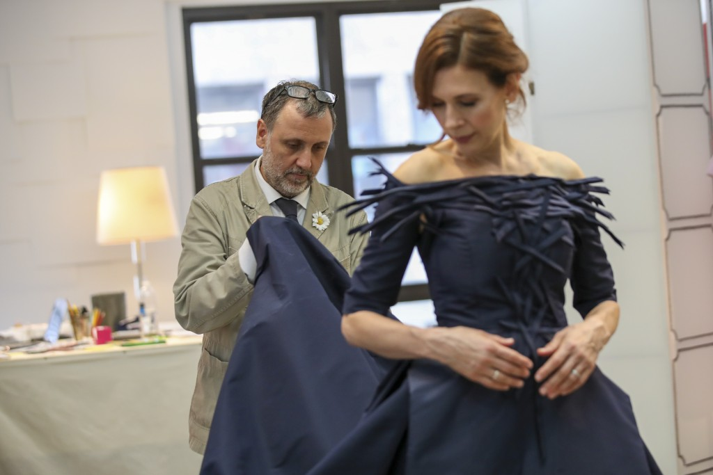 In this Sept. 4, 2019, photo,  designer Herve Pierre, left, fits actress Jessica Hecht, for dresses for her to wear at the Creative Arts Emmys, at Ate...