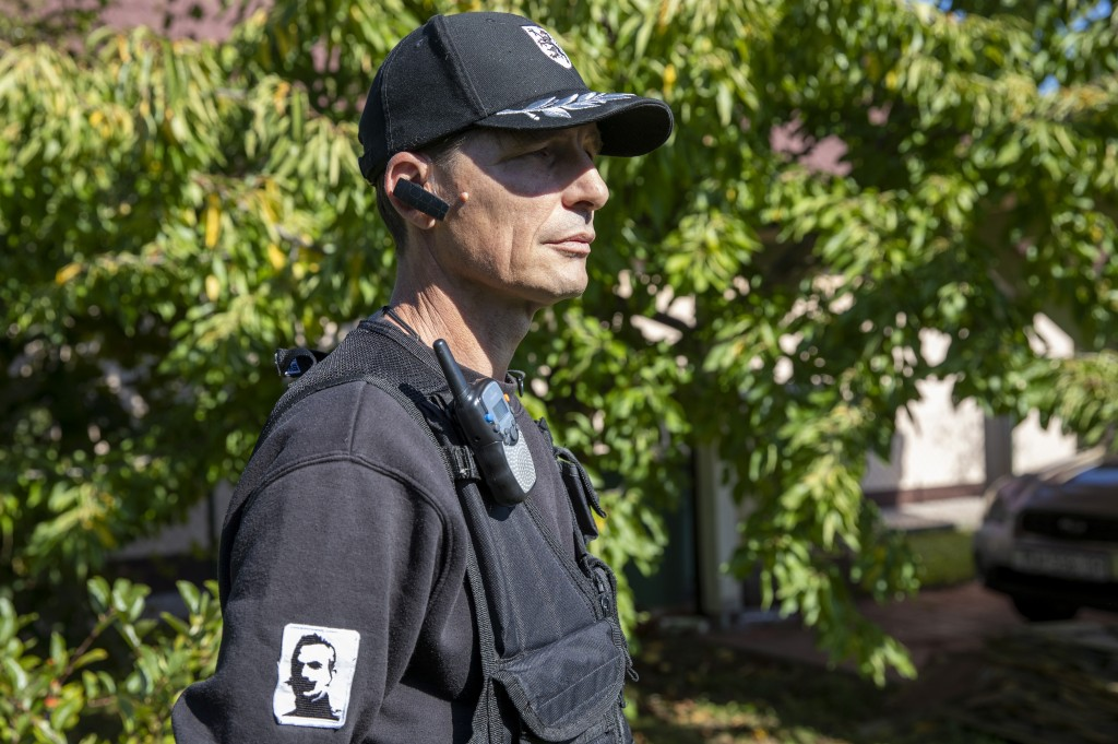 In this Sept. 4, 2019 photo, a member of a volunteer group called the Stajerska Garda looks toward his leader Andrej Sisko, in Maribor, Slovenia. The ...